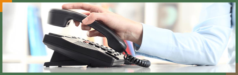 Dłoń trzymająca słuchawkę telefonu stacjonarnego